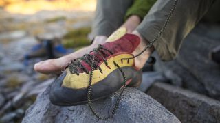 A man tying the laces on his rock climbing shoes