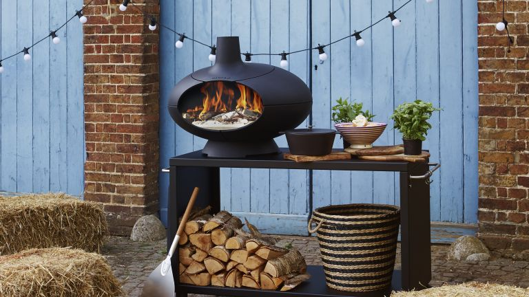 outdoor wood-fired oven with a stack of logs underneath