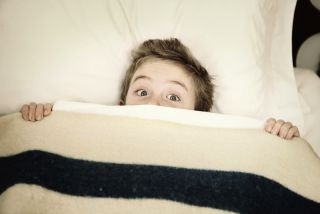 boy hiding in bed