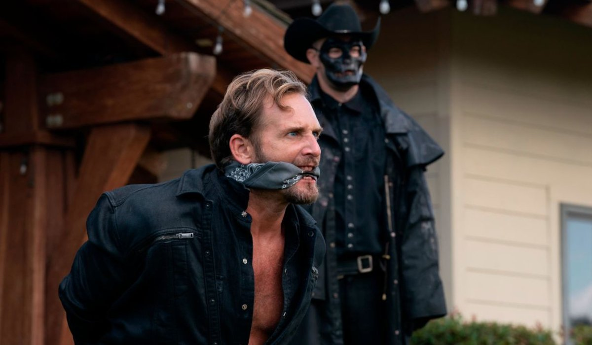 Josh Lucas bound and gagged by a sinister Purger in The Forever Purge.