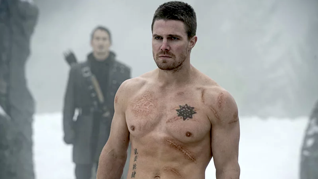 Stephen Amell Goes Shirtless In Hot Pink Shorts With Post Saying He's Back In Prime Green Arrow Shape
