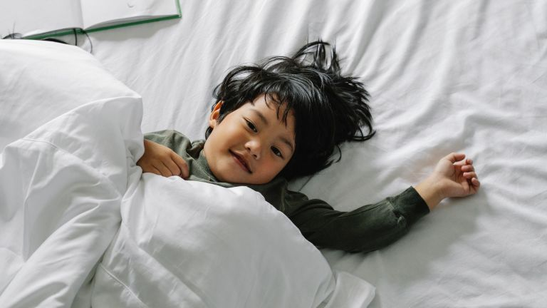 Young boy lying in bed