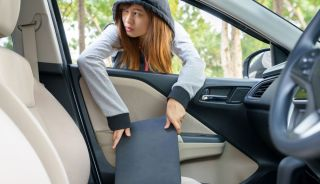 A young woman wearing a hoodie taking a laptop from the front seat of a car.