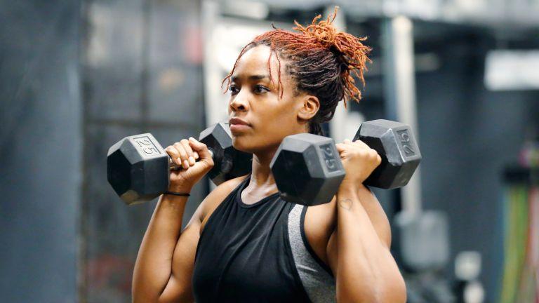 Woman using dumbbells to perform a shoulder press