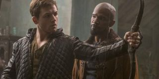 Robin Hood Taron Egerton stands in front of Jamie Foxx with a bow in his hand