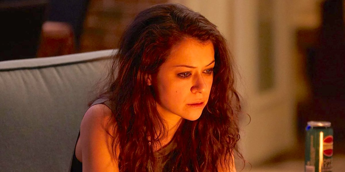 Tatiana Maslany sitting on the couch, bathed in orange light