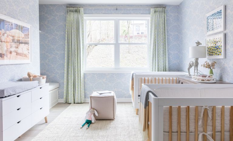 Nursery ideas in pale pastel blue, with pastel green drapes, white furniture and twin cots.