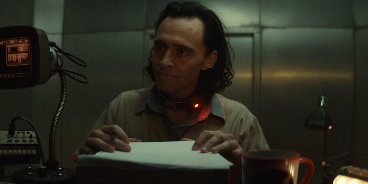 Tom Hiddleston signing papers in Loki