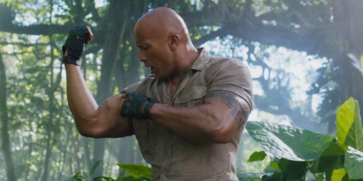 Dr. Xander Bravestone (The Rock) looks shocked at the size of his bicep as he flexes it in 'Jumanji: