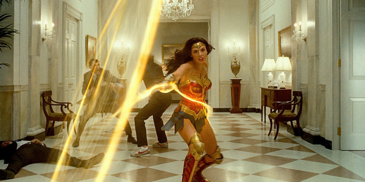 Wonder Woman (Gal Gadot) swings her lasso as men fight in the background in 'Wonder Woman 1984'