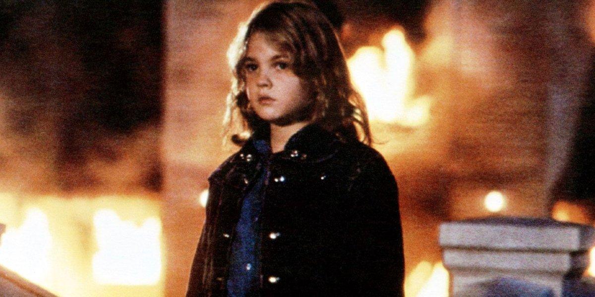 Firestarter Drew Barrymore stands in front of a burning building