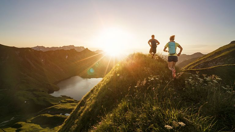 Man and woman running over hills at sunset as part of a trail running training plan