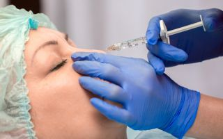 "A stock photo of a woman receiving a ""liquid nose job,"" a cosmetic procedure in which injections of facial fillers are used to change the appearance of the nose."