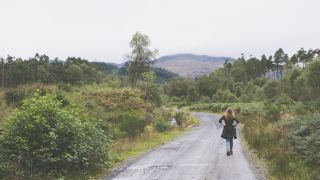 Woman walking in the Trossachs National Park
