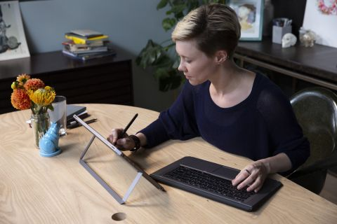 Woman using HP ZBook x2 as a tablet on a stand, with detached keyboard