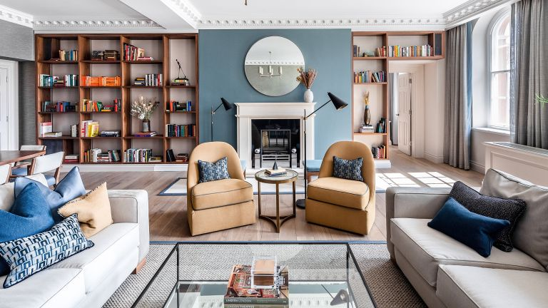 A blue living room with white fireplace, walnut bookshelves and yellow armchairs