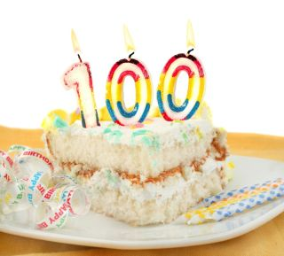 "A piece of birthday cake, with a ""100"" candle on top."