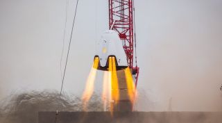 A SpaceX Crew Dragon spacecraft testing its SuperDraco thrusters. SpaceX said July 15 that an accident nearly three months earlier that destroyed a Crew Dragon spacecraft during testing was likely caused by a faulty valve in the SuperDraco propulsion system.