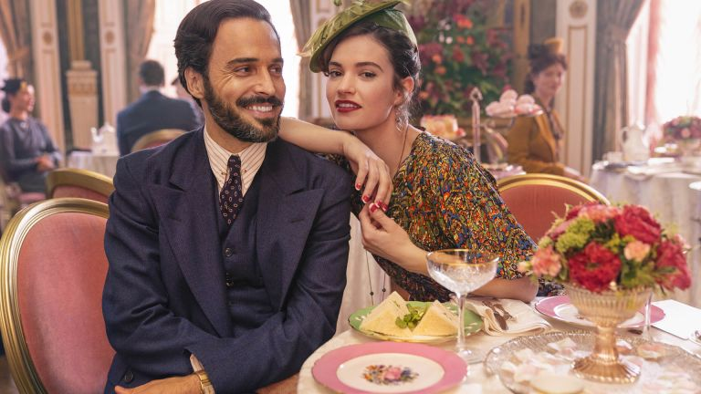 the pursuit of love: Assaad Bouab as Fabrice de Sauveterre and Lily James as Linda Radlett sitting at a table with champagne saucers