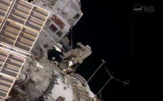 A spacewalking cosmonaut outside the station.
