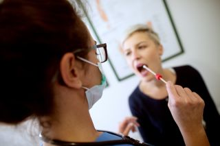 Medical professional takes a cheek swab from a patient.