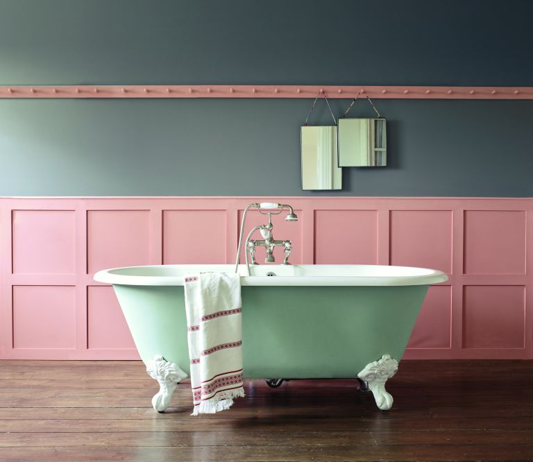 Coral painted bathroom with paneling and green tub