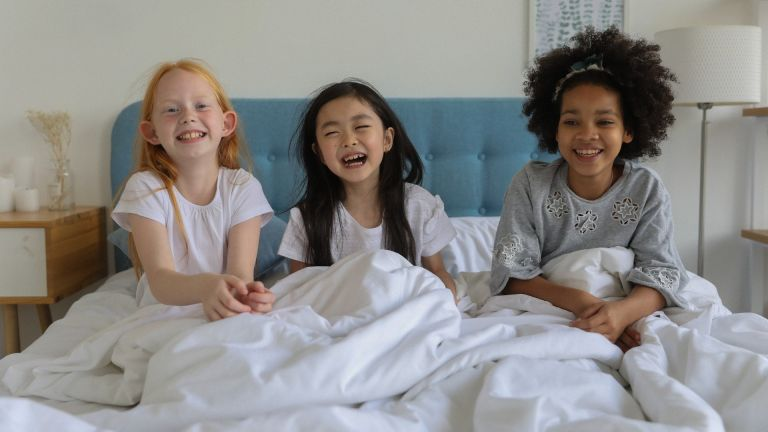 Three young girls sat in bed laughing