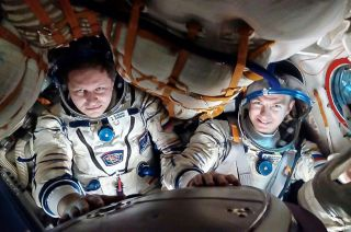 Roscosmos cosmonauts Andrei Babkin (left) and Nikolai Tikhonov, seen here during a Soyuz fit check in 2018, have been removed from the Soyuz MS-16 mission to the International Space Station after Tikhonov was reportedly injured during training.