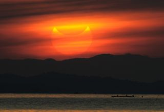A partial solar eclipse as seen during sunrise in the coastal town of Gumaca, in the Philippines, on May 21, 2012.