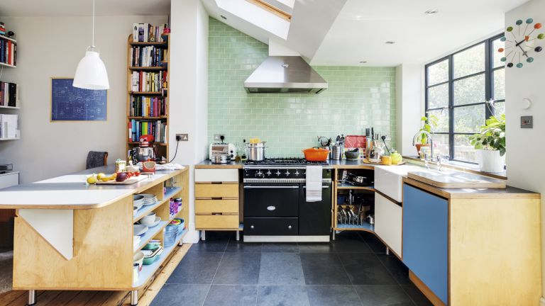 Light-filled kitchen space with plywood units, green wall tiles, range cooker and extractor