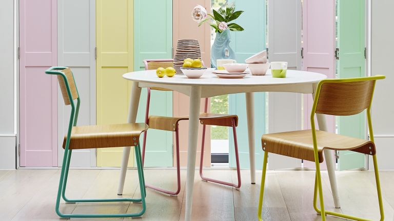 Pastel rainbow shutters in dining room with colorful chairs