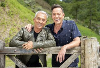 Bruno Tonioli and Craig Revel Horwood pose for a photo while leaning on a fence gate in a lush green landscape on a sunny day
