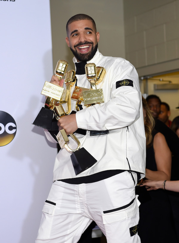 Drake smiling at 2017 Billboard Music Awards with many trophies