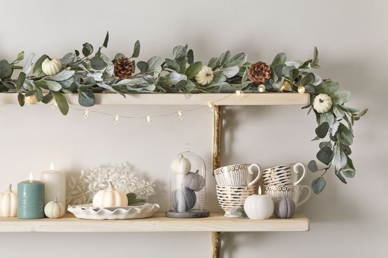 Eucalyptus garland hanging over white shelving with neutral autumnal accents and trinkets