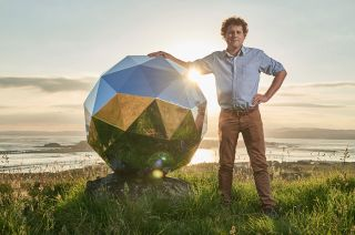 "Rocket Lab founder and CEO Peter Beck stands with his creation, ""The Humanity Star,"" which is visible in the night sky if you know when and where to look."