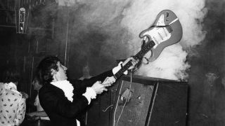 Pete Townshend performing live onstage, smashing guitar against amplifier