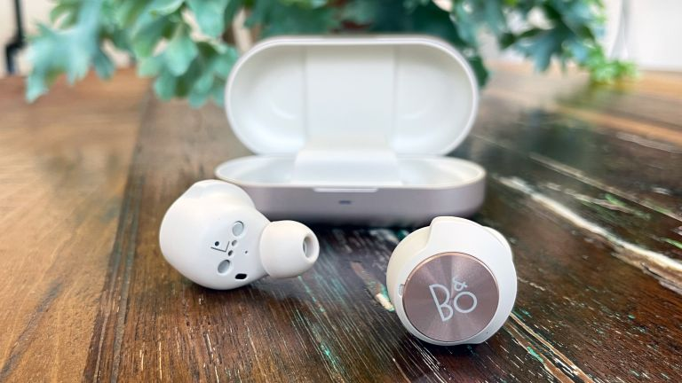 Bang & Olufsen Beoplay EQ review, image of the earbuds on a wooden table, one has the B&O logo facing the camera, with the case in the background