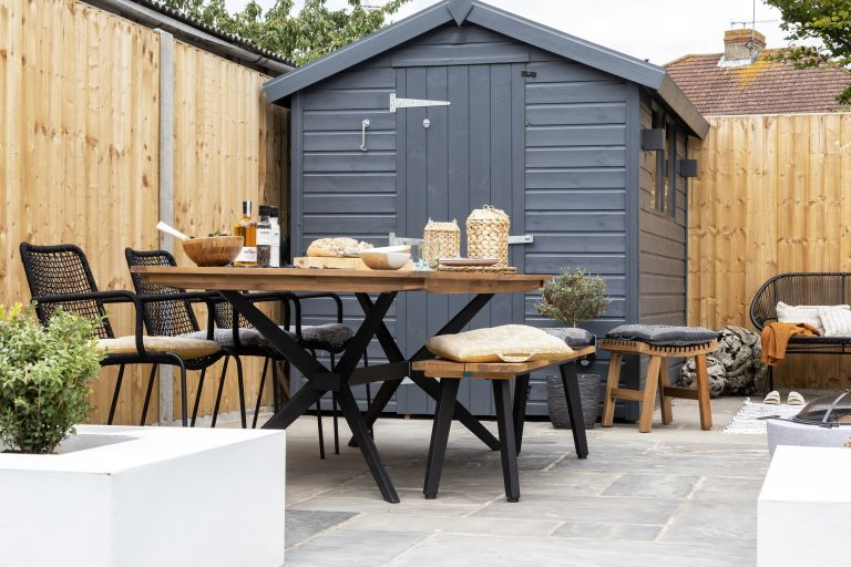 outdoor dining area with a large dining table and a black shed in a modern garden