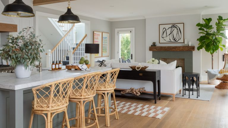 A modern farmhouse-style, open-plan kitchen and dining area with bamboo bar stools and white sofa