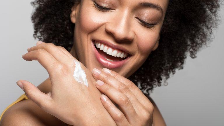 smiling woman using hand cream