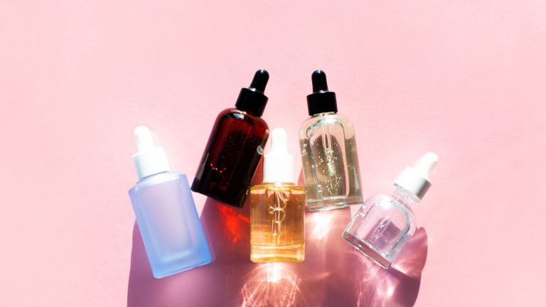 Top view of bottles of moisturizing cosmetic products arranged in line on pink background, hyaluronic acid for hair