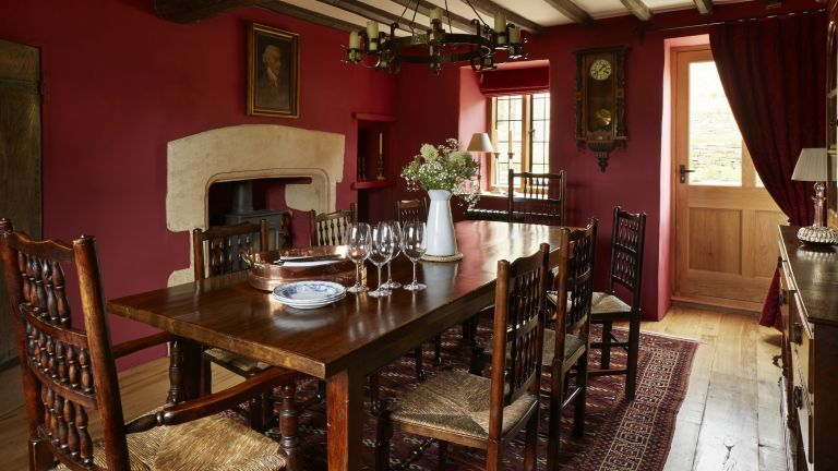 wooden table and chairs in a red walled dining room with beams on the ceiling