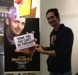 "Jason Silva, the host of National Geographic Channel's show ""Brain Games,"" pointing to his poster. It may trick you."