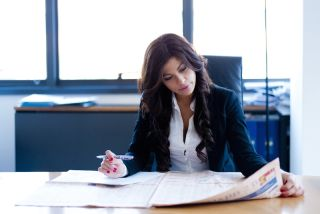 A woman sits working at her desk.