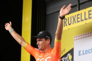 CCC Team's Greg Van Avermaet – on the podium to collect the polka-dot jersey after stage 1 of the 2019 Tour de France in Brussels – salutes the crowd, wearing his blue 'CCC Team for UNICEF' wristband and with the UNICEF logo on his team jersey