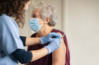 A healthcare provider vaccinating an older person.