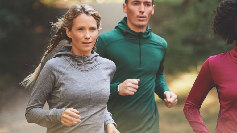 Best winter running tops: women and men running on road in brooks running tops