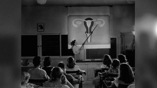 A teacher points to a diagram of female reproductive organs projected on a screen in a classroom in a scene from Human Growth, an education film on sex education shown to students in Oregon junior high schools beginning in 1948.