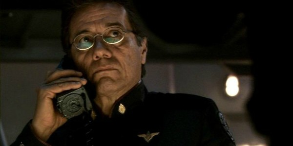 Edward James Olmos holding a futuristic phone to his ear