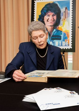 Tam O'Shaughnessy, Sally Ride's life partner, looks through the late astronaut's postage stamp collection. Behind her is an enlargement of the 2018 Sally Ride Forever U.S. stamp. In a 2019 conversation with Space.com, O'Shaughnessy weighs in on the future of LGBTQ+ astronauts.